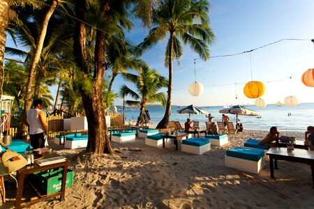 Philippines, Boracay Island - 24 April 2013: Seashore restaurant on white beach with people
