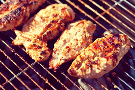 Grilled chicken on barbeque, cooking process at summertime, toned image