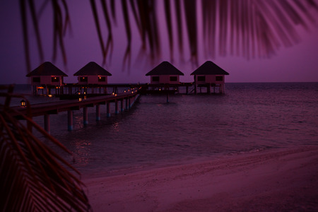Sunset scene in pink colors at Maldives beach, luxury water lodges