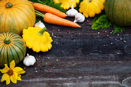 Fresh organic seasonal vegetables - pumpkin, squash, carrots on wooden background
