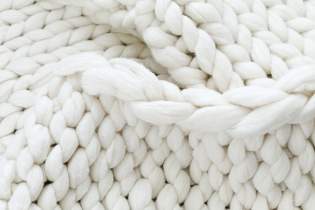 White texture background from merino knitted blanket, scandinavian minimalism backdrop with copy space, top view