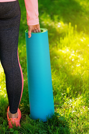 Happy sportive woman after fit training, holding in hands blue yoga mat outside at park. Fitness, sport and healthy lifestyle
