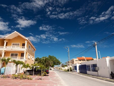 BAVARO, PUNTA CANA, DOMINICAN REPUBLIC - 4 FEBRUARY 2019: Street with road and houses. Traditional caribbean buildings