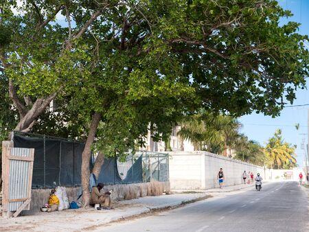 BAVARO, PUNTA CANA, DOMINICAN REPUBLIC - 4 FEBRUARY 2019: Homeless man sleeping under tree at the street