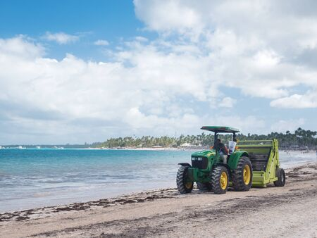 BAVARO, PUNTA CANA, DOMINICAN REPUBLIC - 24 JANUARY 2019: Cleaning sargassum algae on tropical coastline by tractor with Barber Surf Rake. Caribbean ecology problem. The Barber Surf Rake is the most popular tractor-towed beach cleaner in the world