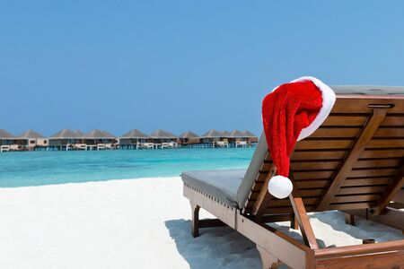 Wooden chaise longues on tropical beach decorated Santa Claus hat, Concept of exotic Christmas celebration on winter vacation