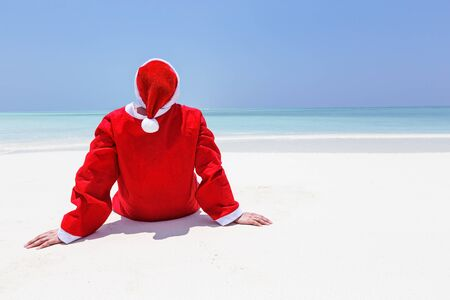Santa Claus celebrate Christmas on sandy beach, enjoy winter holidays at tropical destination. Travel Greeting Card.