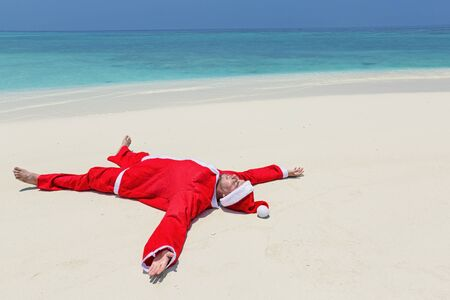 Santa Claus celebrate Christmas on sandy beach, relax and enjoy winter holidays at tropical destination, greeting card Фото со стока