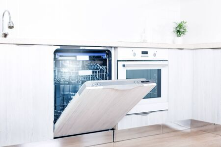 Empty dishwasher with opened door, home appliance dishwashing machine in kitchen interior, no people