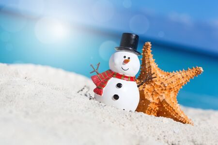 Tropical Christmas greeting card, decorative snowman with star fish on sandy beach, sea view with copy space Stock Photo