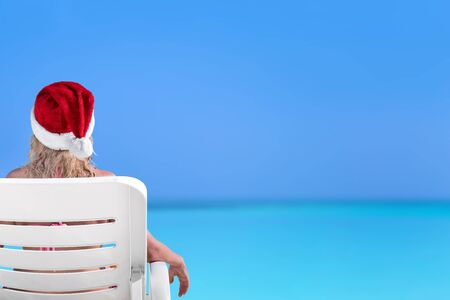 Woman in Santa Claus Hat on sunbed at beach with turquoise sea view. Christmas vacation on islands Stock Photo