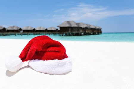 Santa hat on sand with water lodges on background. Christmas vacations on Maldives island, travel destinations concept.