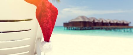 Santa hat on chair with water lodges on background. Christmas holidays travel  concept, long banner, copy space 版權商用圖片