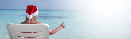 Woman in Santa Claus Hat show thumbs up on sunbed at beach with turquoise sea view. Christmas vacation on islands Stock Photo