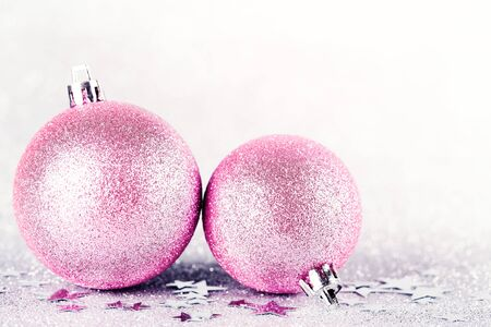 Pink Christmas baubles on silver glitter with defocused lights on background, New Year greeting card. Shallow depth of field.