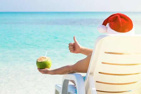 Christmas celebration on beach, man in Santa Hat relaxing on sunbed with coconut cocktail in hand, winter holidays vacation