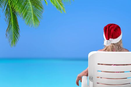 Woman in Santa Claus Hat on sunbed at beach with turquoise sea view. Christmas vacation on islands 版權商用圖片