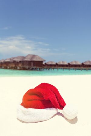Santa hat on chair with water lodges on background. Christmas holidays on Maldives island, travel concept. 版權商用圖片