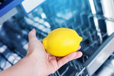 Fresh yellow lemon in female hand on empty dishwasher background, aroma freshness care concept, clean equipment, no face