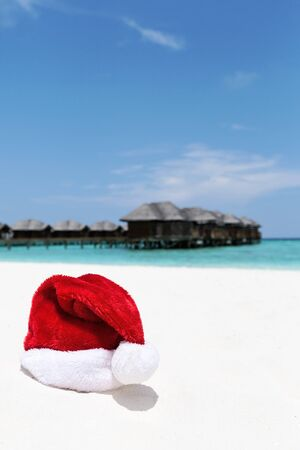 Santa hat on chair with water lodges on background. Christmas holidays on Maldives island, travel destinations concept. 版權商用圖片