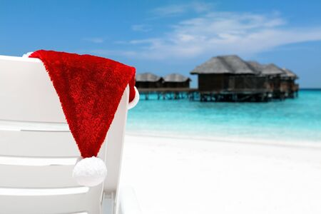 Santa hat on chair closeup with water lodges on sea. Christmas holidays background on island, travel destinations concept.