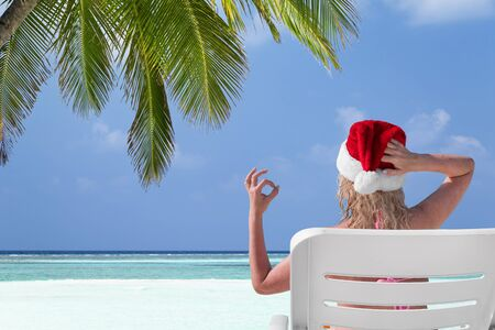 Woman in Santa Claus Hat show gesture Okay on sunbed at beach with palm tree leaf. Christmas vacation on islands