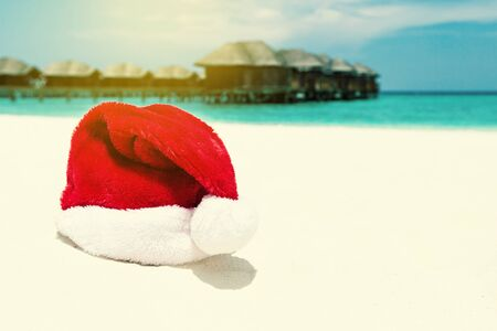 Santa hat on beach with water lodges on background. Christmas holidays on Maldives island, travel destinations concept. 版權商用圖片