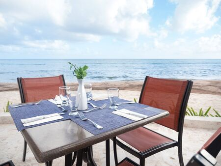 Table with dinner setting at outdoors restaurant near tropical sea, nobody