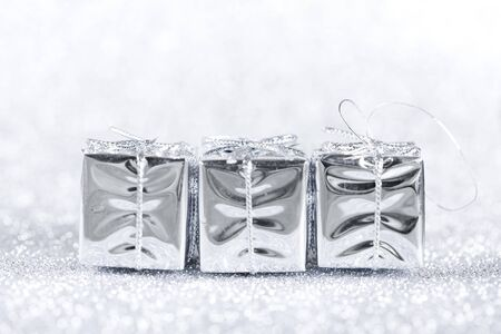 White present boxes on shiny silver background.  Christmas and New Year decoration 版權商用圖片