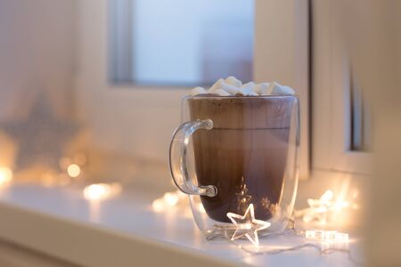 Hot cocoa in cup with mini marshmallows on window sill, decorated lights garland, sweet chocolate beverage in double wall glass mug, cozy morning, nobody. Shallow depth