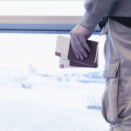 Man in airport waiting for flight with boarding tickets in hand, no face