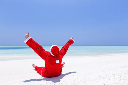 Santa Claus celebrate Christmas on sandy beach, enjoy winter holidays at tropical destination. Travel Greeting Card.