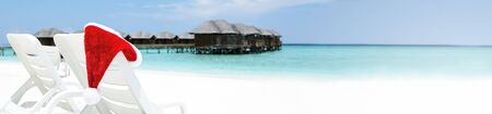 Santa hat on chair with water lodges on background. Christmas holidays on Maldives island, travel destinations concept, long banner