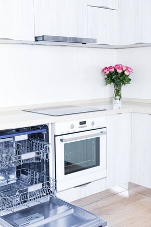 Empty dishwasher with opened door and beautiful bouquet of flowers roses, concept of present surprise for housewife, no people