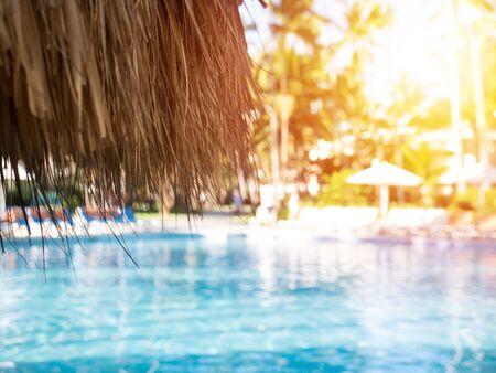 Sunshade umbrella at tropical resort poolside, nobody