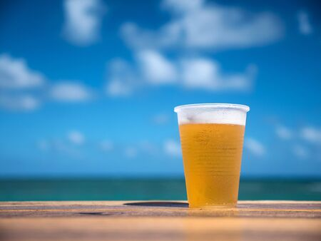 Beer in plastic cup on wooden table over caribbean sea background, closeup