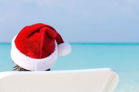 Christmas celebration on beach, man in Santa Hat relaxing on sunbed and enjoying winter holidays vacation