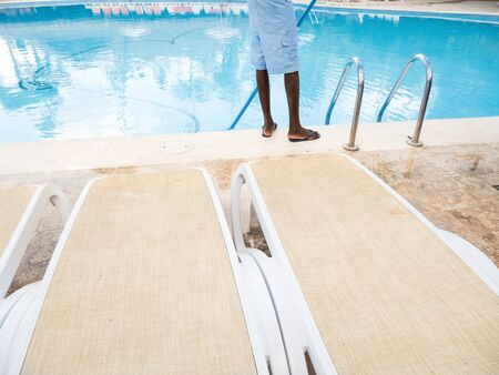 Man cleaning swimming pool. Maintenance of pool at resort