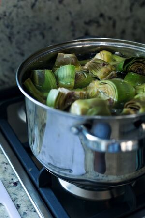 Cleaned artichokes preparing in metal pan on cooker, artichoke cooking process at kitchen interior, nobody