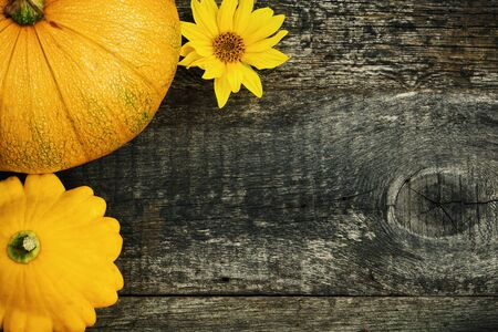 Yellow pattypan and pumpkins decorated sunflower, summer fresh vegetables on old wooden board