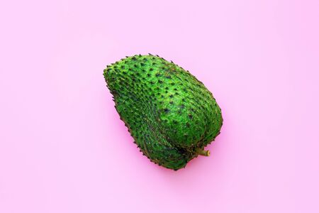 Closeup of green soursop graviola, exotic, tropical fruit Guanabana on pink background. Alternative medicine treatment of cancer Stock Photo