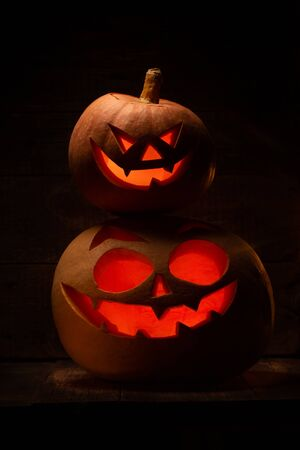 Two Halloween pumpkins with scary face. Jack-o-lantern in the dark. Celebration autumn holiday
