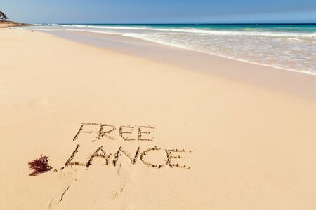 Word FREELANCE written on sand close to sea waves. Travel, business and vacation concept background.