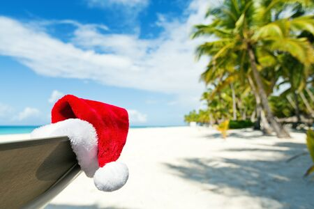 Santa Claus hat on beach. Christmas celebration on tropical island paradise.