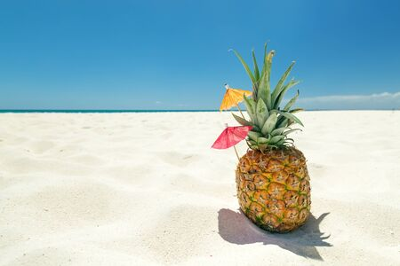 Sweet pineapple cocktail on sand with caribbean beach background. Travel summer vacation banner with copy space for your text Banque d'images
