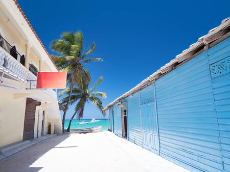 Typical caribbean house near Atlantic ocean beach with coconut palm tree. Blue and red exterior of tropical wooden hut Standard-Bild