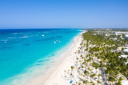 Aerial view from drone on tropical coastline with coconut palm trees, sunbeds and boats floating in caribbean sea. Summer vacations. Travel destinations