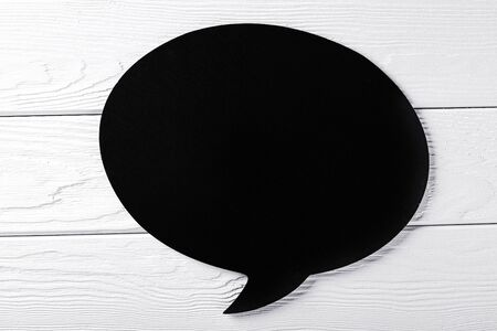 Blank black say sign plate on white wooden background. Nobody