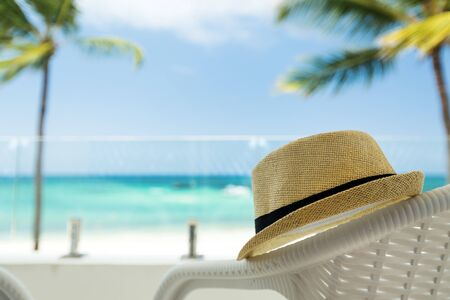 Summer hat closeup on white rattan chair at balcony resort, caribbean nature background with sea view Archivio Fotografico