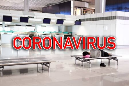 Sign CORONAVIRUS on monitors at airport terminal. One unrecognizable man sleeping on seat. Quarantine concept